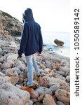 rear view of young man walking... | Shutterstock . vector #1050589142