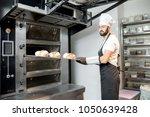 baker taking off baked breads... | Shutterstock . vector #1050639428