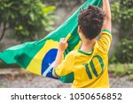 Stock photo brazilian boy holding the flag of brazil 1050656852
