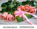 pink roses and gift box in... | Shutterstock . vector #1050693236
