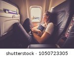 woman sleeping in an airplane.... | Shutterstock . vector #1050723305