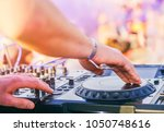 Small photo of Dj mixing at beach party festival with people dancing in the background - Deejay playing music mixer audio outdoor - Concept of summer events and club outdoor