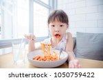 little asian girl eating... | Shutterstock . vector #1050759422