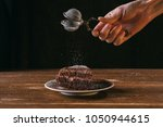 a woman's hand is dusting icing ... | Shutterstock . vector #1050944615