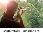 man with long rifle gun... | Shutterstock . vector #1051064576
