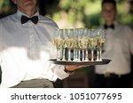an immaculate waiter gracefully ... | Shutterstock . vector #1051077695