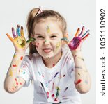 little girl covered in paint... | Shutterstock . vector #1051110902