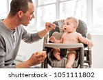 father and baby eat with the... | Shutterstock . vector #1051111802