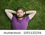 young man lying on ground in... | Shutterstock . vector #1051132256
