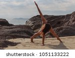 young woman practicing yoga on... | Shutterstock . vector #1051133222