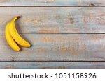 ripe bananas on a gray wooden... | Shutterstock . vector #1051158926