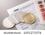 Small photo of Bitcoin and alternate cryptocurrencies coin symbol on tax form with calculator, crypto currency sign, future technology financial concept