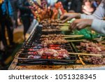 hand of a hawker grilled pork... | Shutterstock . vector #1051328345