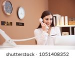 Female receptionist talking on phone at hotel check-in counter