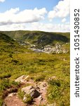 Small photo of Landscape view of small rural town Petty Harbour, Newfoundland looking down from the rugged green hills and cliffs with pine trees, rocks and shrubs in the foreground