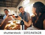 cheerful friends toasting wine... | Shutterstock . vector #1051465628