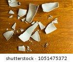 white shards of a broken plate... | Shutterstock . vector #1051475372