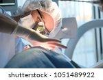 female dentist in surgical... | Shutterstock . vector #1051489922
