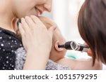 doctor examining childs ear...   Shutterstock . vector #1051579295