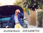 Small photo of Stressed man having trouble with his broken car looking in frustration at failed engine; hand on head looking at you sitting on the open capote top of the car. Negative emotion reaction body language