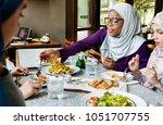 islamic women having dinner | Shutterstock . vector #1051707755