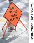 Small photo of Side view on an orange construction sign warning Bicycles Merge with Traffic, along a city street