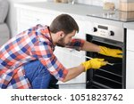 young man cleaning oven in... | Shutterstock . vector #1051823762