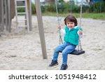 little boy swinging on a swing... | Shutterstock . vector #1051948412