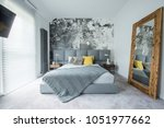 Stock photo grey bedsheets on bed with yellow pillow in bedroom interior with mirror and concrete wall 1051977662