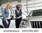 sales consultant shows the girl ... | Shutterstock . vector #1051981385