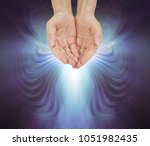 hands bathed in a resonating... | Shutterstock . vector #1051982435