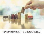 hand choosing mini wood house...   Shutterstock . vector #1052004362