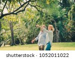 senior couple smiling and... | Shutterstock . vector #1052011022