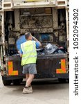 Small photo of Tarrant Hinton, Dorset, UK - September 1, 2012: A Waste Collector empties a bin into the back of a bin lorry