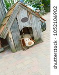 Small photo of Toy dog lying in a wooden kennel.