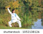 young woman doing a taichi or... | Shutterstock . vector #1052138126