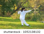 young woman doing a taichi or... | Shutterstock . vector #1052138132