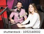happy young female radio host... | Shutterstock . vector #1052160032
