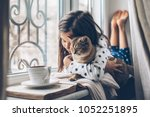 Stock photo child in pajamas relaxing on a window sill with pet lazy weekend with cat at home cozy scene 1052251895
