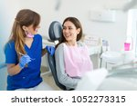 dentist and patient in dentist... | Shutterstock . vector #1052273315