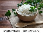 white rice in wooden bowl. top... | Shutterstock . vector #1052297372
