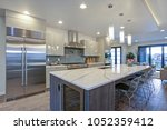 Stock photo sleek modern kitchen design with a long center island fitted with a gray and white quartz 1052359412