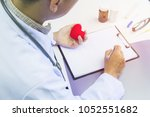 doctor holding red heart and... | Shutterstock . vector #1052551682