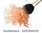 Small photo of Crushed face powder bronzer and cosmetic blush brush on white background