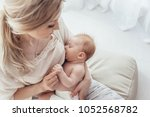 Small photo of Bright portrait of a mom breast feeding baby over window lighting.