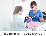 dentists and patient in dentist ... | Shutterstock . vector #1052570426