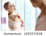 young woman applying body cream ... | Shutterstock . vector #1052572928