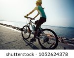 female cyclist riding mountain... | Shutterstock . vector #1052624378
