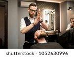 barber rubbing foam in hands...   Shutterstock . vector #1052630996