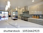 Stock photo sleek modern kitchen design with a long center island fitted with a gray and white quartz 1052662925